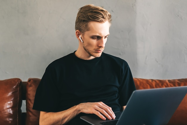 Der nachdenkliche mobile entwicklerprogrammierer des kaukasischen mannes schreibt programmcode auf einen laptop im heimbüro.