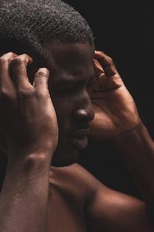 Der nackte afroamerikaner berührt seinen kopf mit geschlossenen augen und spürt schmerzen oder stress auf schwarz