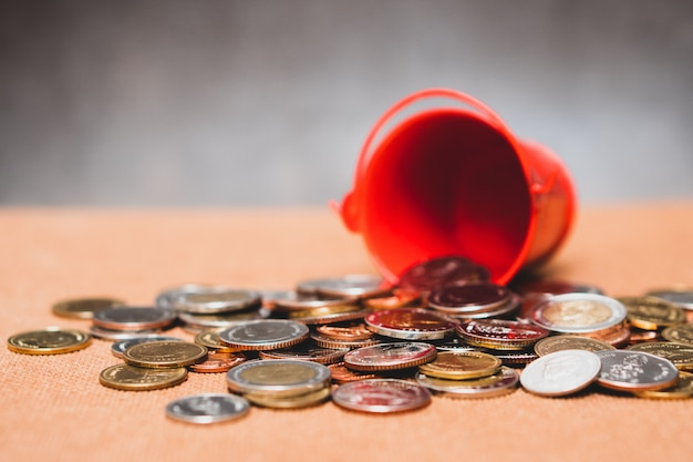 Der nahaufnahmestapel prägt vom roten eimer mit als geschäfts- und finanzkonzept verwirrend
