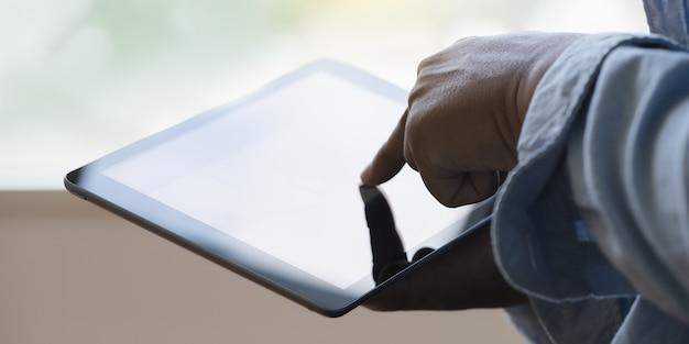 Der nahe hohe mann des digital-tablet-computers, der tablette verwendet, übergibt den mann, der mit lokalisiertem schirm multitasking ist