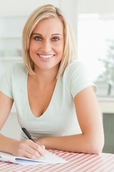 Der nette frauenbeweis, der einen text liest, lächelt in kamera
