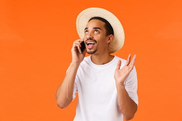 Der nette freundliche afroamerikanermann des oberkörperaufnahme schusses, der am telefon ausdrucksvoll spricht und das sprechen gestikuliert, das oben schaut, preisen ehrfürchtiges hotel und luxus-resort und halten smartphone nahe ohr