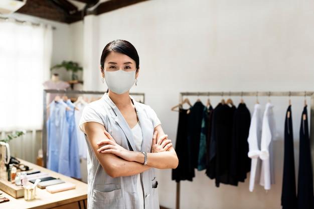 Der neue normale mitarbeiter des einzelhandels, der eine maske trägt, ist 19