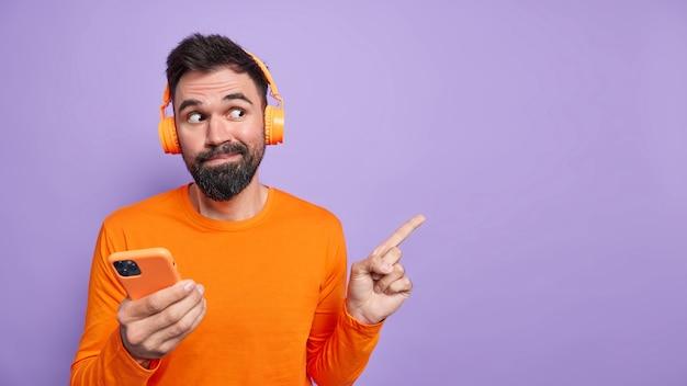 Der neugierige, gutaussehende mann mit bart zeigt etwas interessantes an leeren stellen an der lila wand verwendet das mobiltelefon zum online-chatten und das hören von musik trägt lässig gekleidete kopfhörer