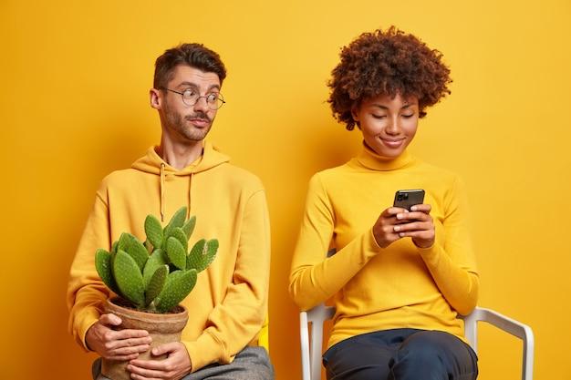 Der neugierige mann schaut in das smartphone der freundinnen und versucht, den inhalt der nachricht zu sehen, der in einem sweatshirt gekleidet ist und einen topf mit kakteen hält.