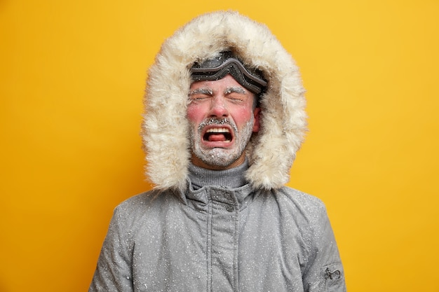 Der niedergeschlagene mann weint und fühlt sich unglücklich, wenn er in winterkleidung gekleidet ist. er fühlt sich sehr kalt an, nachdem das snowboarden ein rotes gesicht hat, das mit raureif bedeckt ist und eine skibrille trägt.