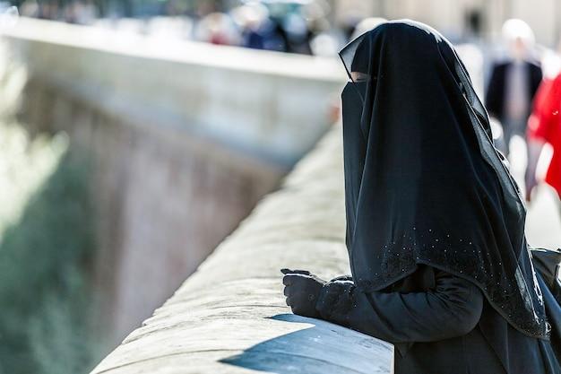 Der niqab ist eine lange tunika, die den körper und den kopf vollständig bedeckt.