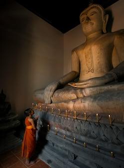 Der novize schaut auf das große buddha-bild in der kirche, um für den respekt der religion zu beten.
