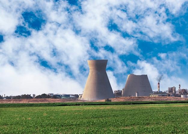 Der obere teil des östlichen inaktiven kühlturms der haifa oil refineries war am 12. juni 2020 eingestürzt. beide türme stehen auf der erhaltungsliste. große industrietürme gegen grüne felder