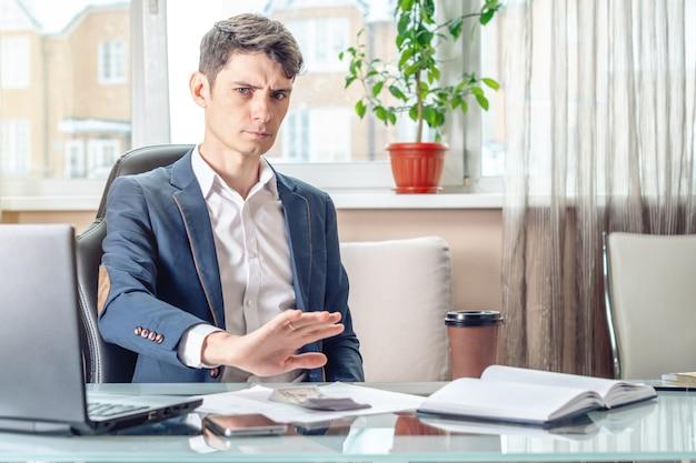 Der offizielle geschäftsmann, der am arbeitsplatz im büro sitzt, lehnt bestechungsgelder ab.