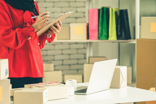 Der online-verkäufer arbeitet zu hause im büro und verpackt die versandbox an den kunden.