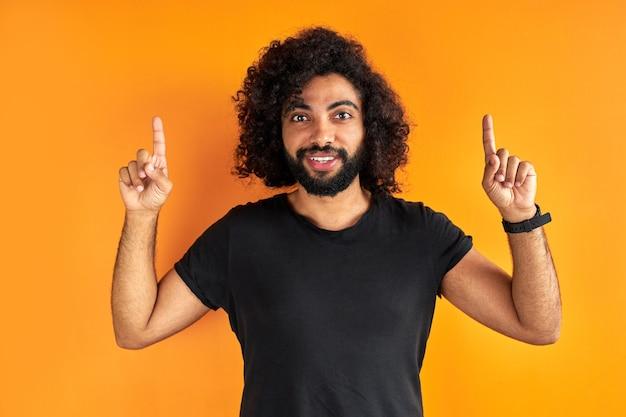 Der optimistische bärtige junge mann zeigt mit beiden zeigefingern nach oben