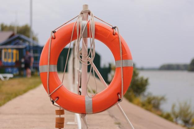 Der orangefarbene rettungsring ist an einen zaun am flusspfeiler gebunden. frontansicht