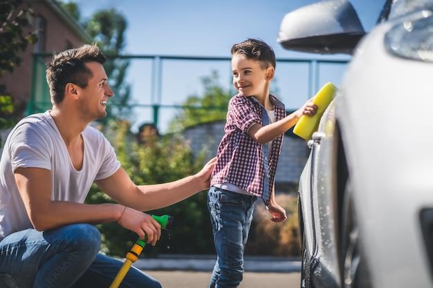 Der papa und sein sohn putzen das auto