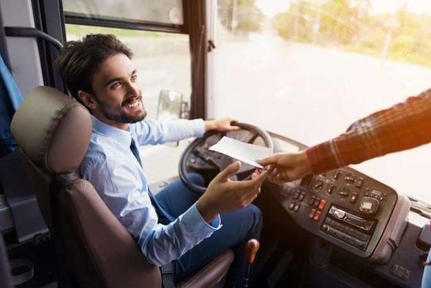 Der passagier gibt ihm eine fahrkarte für die busfahrt