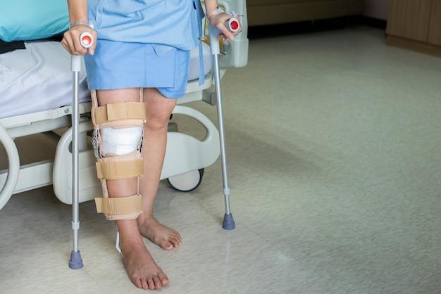Der patient, der auf krücke in der krankenstation steht, ware knie-klammerunterstützung nach tun hintere kreuzbandoperation, verband auf knie von auf krücken. gesundheitswesen und medizinisches konzept.