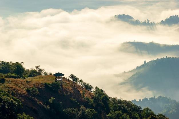 Der pavillon befindet sich in der mitte des berges und es gibt nebel mit morgenlicht.