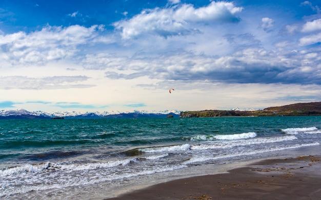 Der pazifik mit wellen und blauem himmel über der bergigen schneebank auf der halbinsel kamtschatka