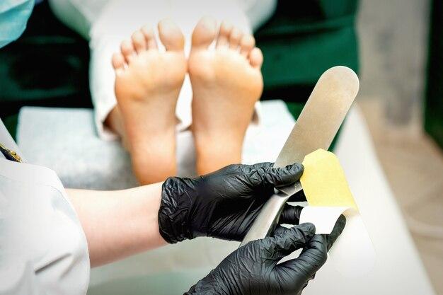 Der pediküre-meister, der vor der reinigung von fuß und ferse in einem nagelstudio neues schleifpapier auf den metallgriff legt