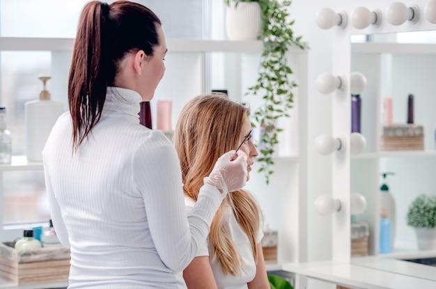Der permanente make-up-meister zeigt dem kunden die ergebnisse des microblading der augenbrauen und des tätowierens der lippen