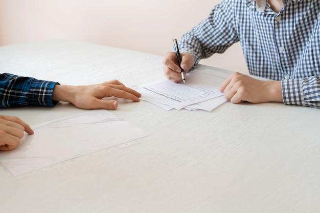 Der personalmanager stellt den neuen mitarbeiter für den neuen job ein, setzt sich an den tisch und interviewt
