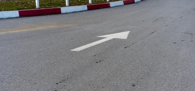 Der pfeil auf dem bürgersteig zeigt die bewegungsrichtung der autos