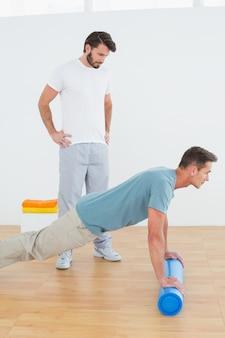 Der physiotherapeut, der jungen mann aufpasst, drücken ups