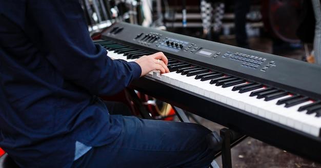 Der pianist spielt den synthesizer