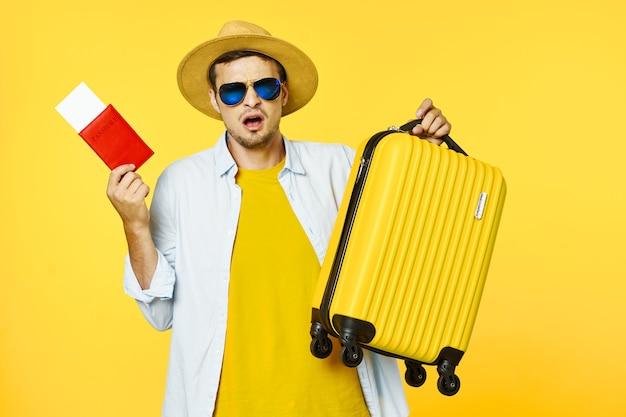 Der platzierte reisende mit einem koffer hält einen pass und ein ballett in den händen
