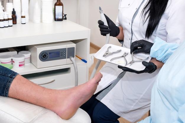 Der podologe behandelt den patienten in einer modernen klinik