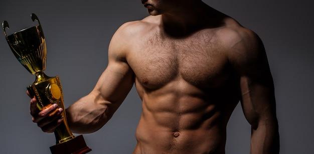 Der pokal des meisters hält den goldenen pokal des mannes. gewinner starker mann, sport, berufsmeister. muskulöser mann, männlicher nackter mann, muskulöser mann gewinnen, torso-mann. sportler, bauchmuskeln, bodybuilding, fitness, bauchmuskeln.