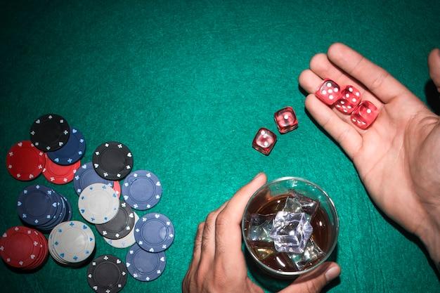Der pokerspieler, der rot zeigt, würfelt mit glas whisky auf pokertisch