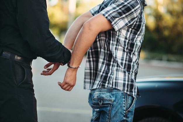 Der polizist verhaftet den autodieb auf der straße
