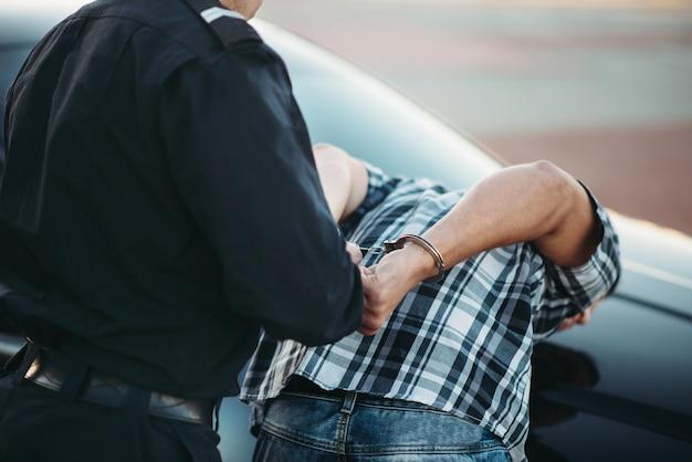 Der polizist verhaftet den fahrer auf der straße