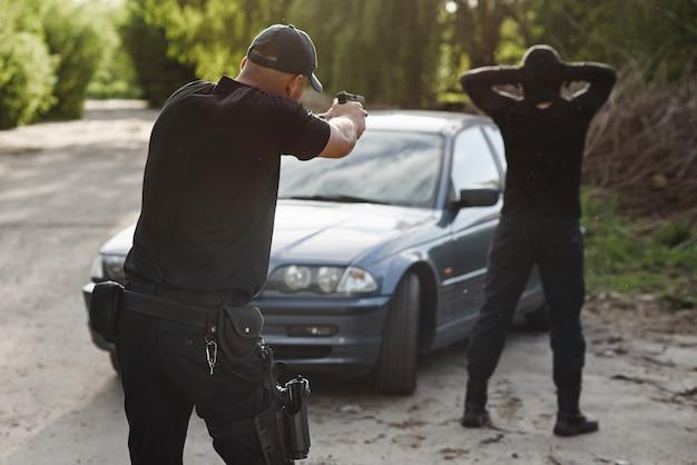 Der polizist zielt auf einen täter in der nähe des gestohlenen autos. stoppen sie die kriminalität.