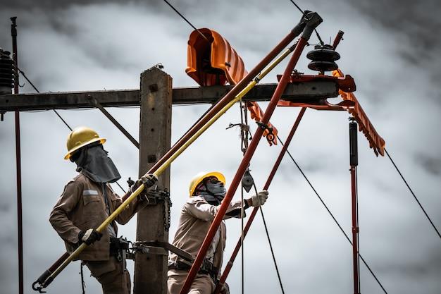 Der power lineman ersetzt den beschädigten isolator
