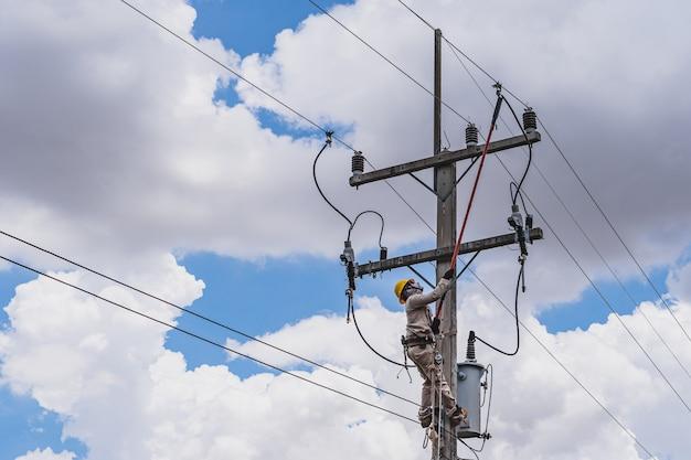 Der power lineman verwendet einen klemmstab (isoliertes werkzeug), um einen transformator an unter spannung stehenden hochspannungsleitungen zu schließen.