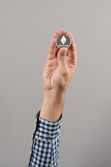 Der preis der kryptowährung ethereum steigt. nahaufnahme von mann mit silbermünze von ethereum. digitales geld.