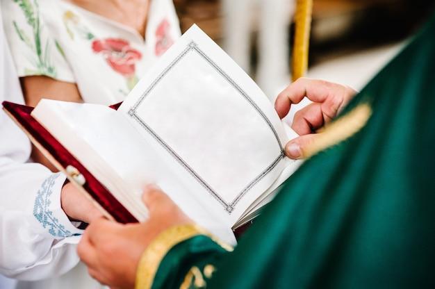 Der priester hält und liest die bibel in seinen händen