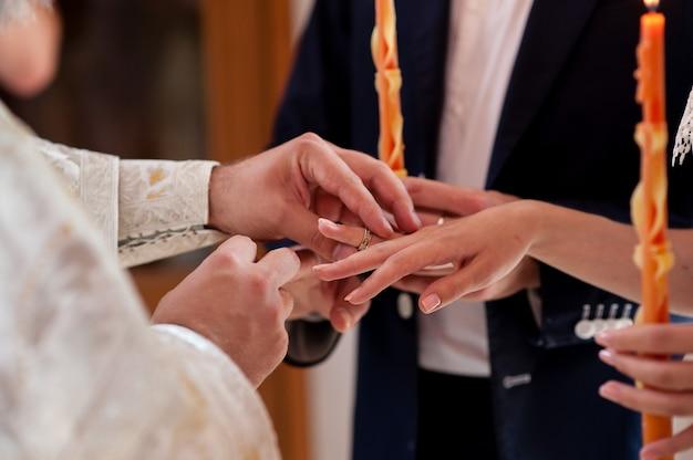 Der priester kleidet die ringe für das brautpaar.