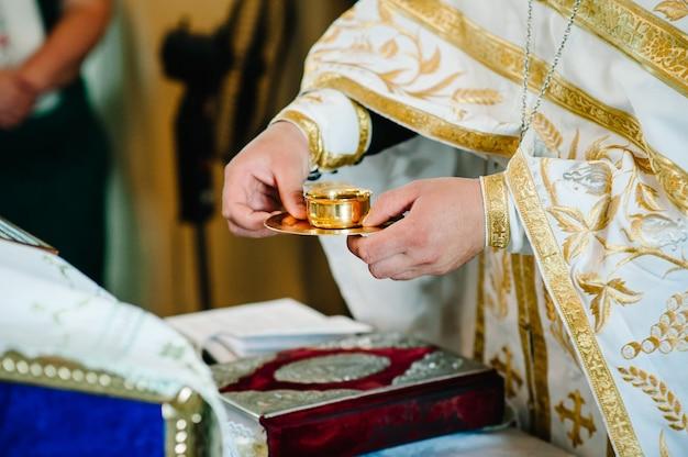 Der priester segnet und gibt in der tasse das blut gottes, wein für braut und bräutigam.