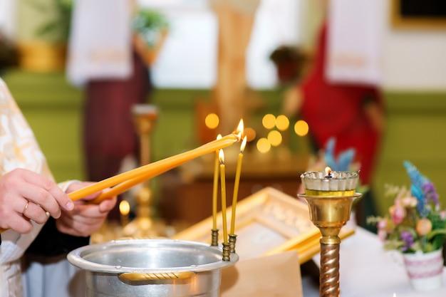 Der priester zündet in der orthodoxen kirche kerzen an