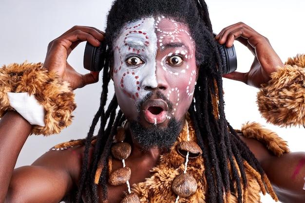 Der primitive mann steht unter schock, wenn er musik in kopfhörern mit geöffnetem mund hört