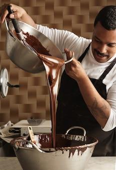 Der professionelle chef des schwarzen mannes gießt leckere geschmolzene schokolade von einem großen stahltopf in einen anderen, bevor er schokoriegel herstellt