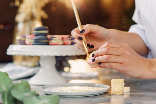 Der professionelle konditor malt mit einem pinsel ein lebensmittel goldfarben auf einen frischen leckeren macaron.