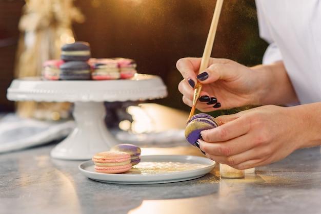 Der professionelle konditor malt mit einem pinsel ein lebensmittel goldfarben auf einen frischen violetten macaron.