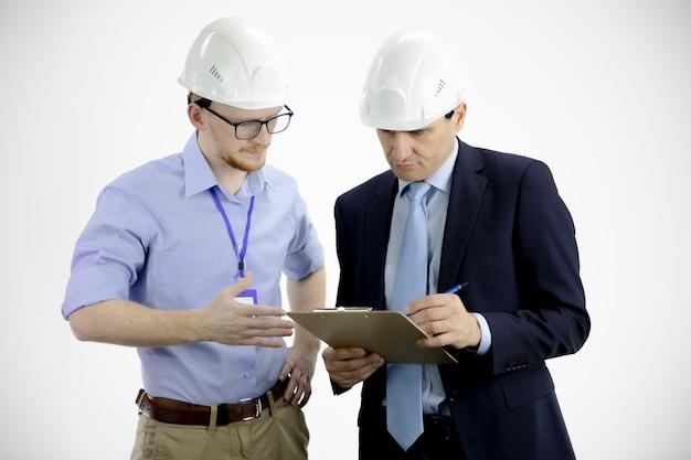 Der projektleiter hält die zwischenablage und bespricht die produktdetails mit dem chefingenieur