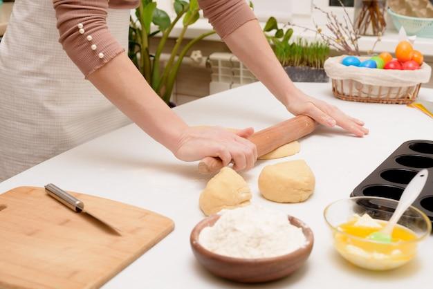 Der prozess, den teig zu hause auf dem tisch auszurollen, ist die hand einer frau, die cruffins zu ostern zu festlichem gebäck macht. seitenansicht einer hellen küche mit bemalten eiern.