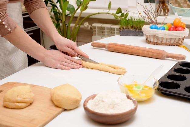 Der prozess, den teig zu hause auf dem tisch auszurollen, ist die hand einer frau, die cruffins zu ostern zu festlichem gebäck macht