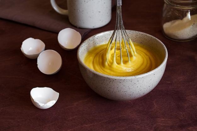 Der prozess der herstellung des kuchens. schüssel mit teig für die torte und schneebesen.